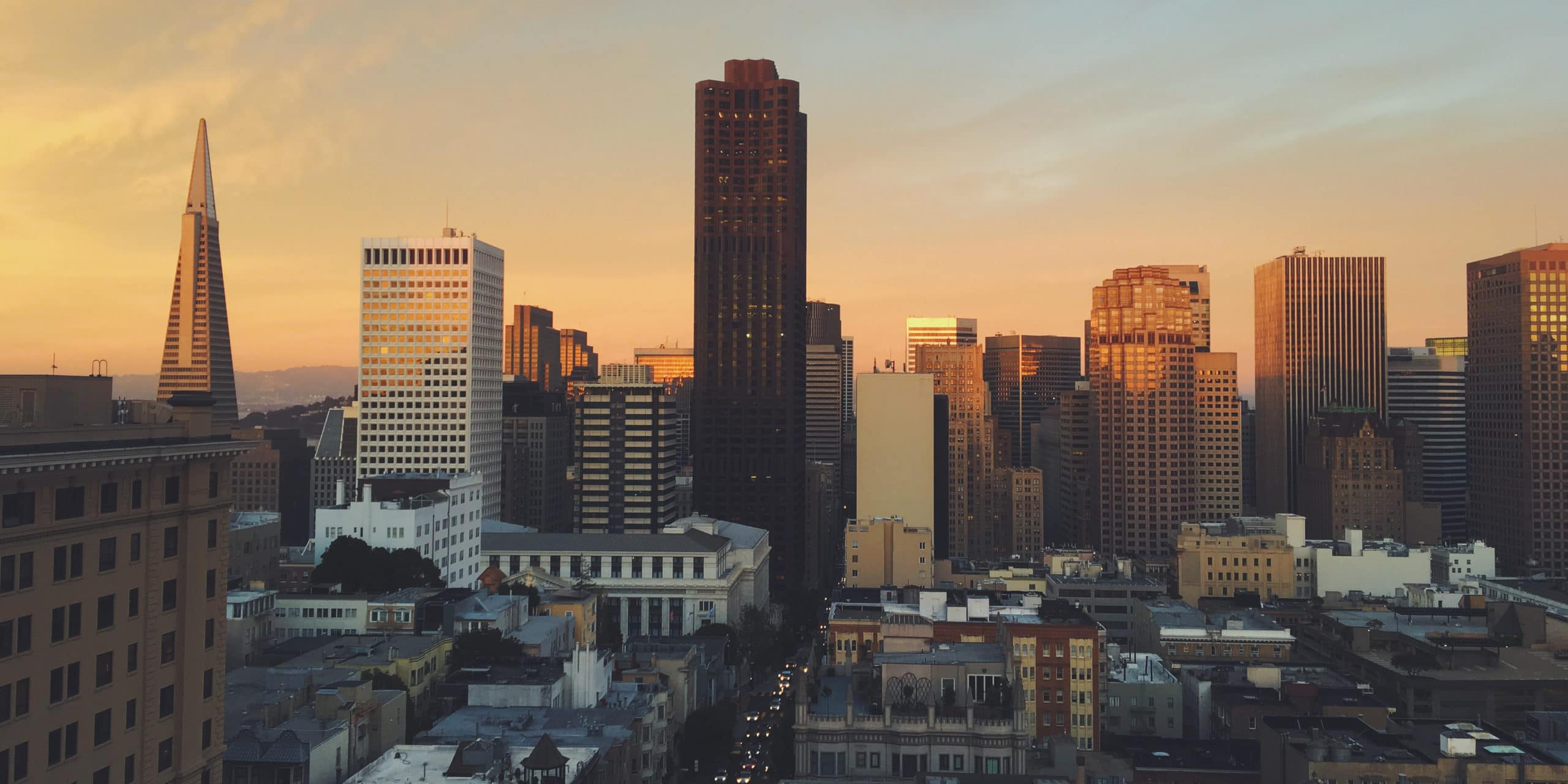View of San Francisco city skyline at sunrise. Several sky scrapers and high rises with pale blue skies in the background.