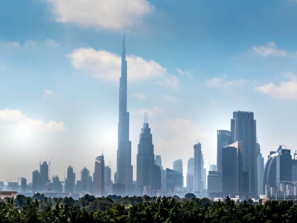 Daytime photo of Dubai skyline. City skyline in the distance, the Burj Khalifa centered, with blue skies in the background.