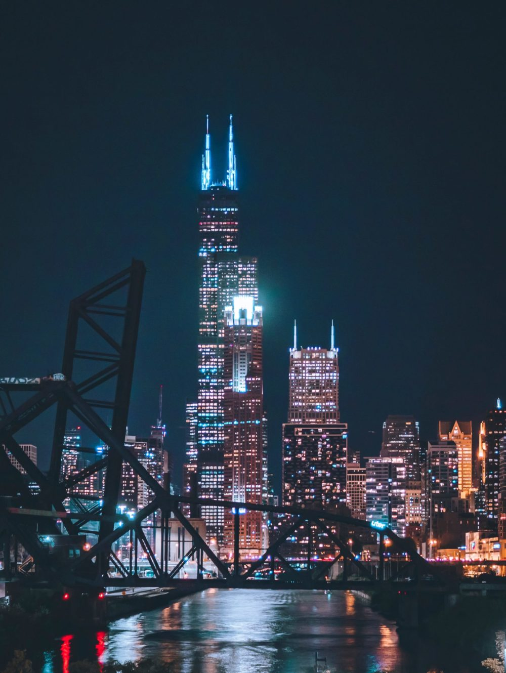 Birds eye view of Willis Tower in Chicago. Night time photo of Chicago skyline with raised bridge in the forefront.