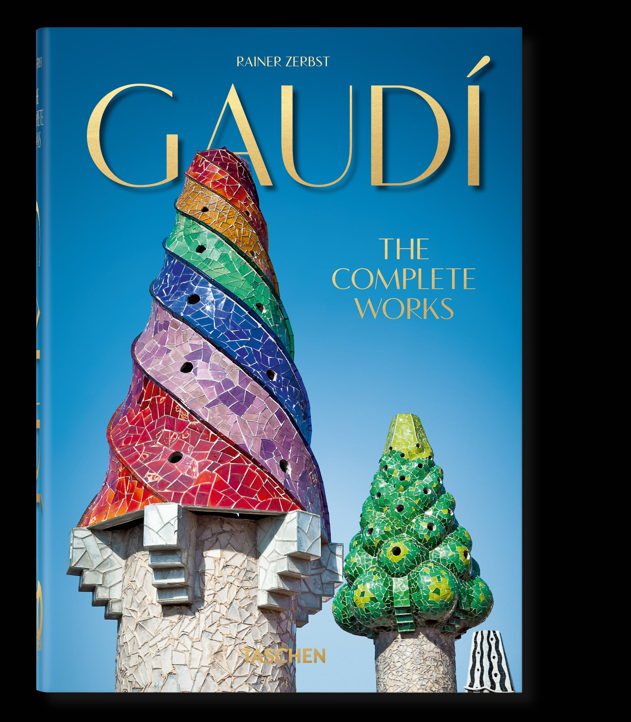 Book cover of Gaudi: The Complete Works. Blue background with cone shaped structures with colorful top halves.