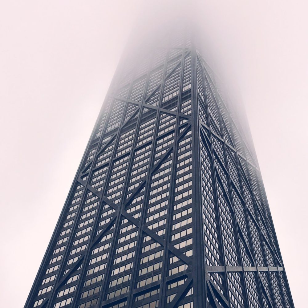 Looking up at the John Hancock Tower in Chicago during a cloudy day. The black facade tower disappears into the clouds.
