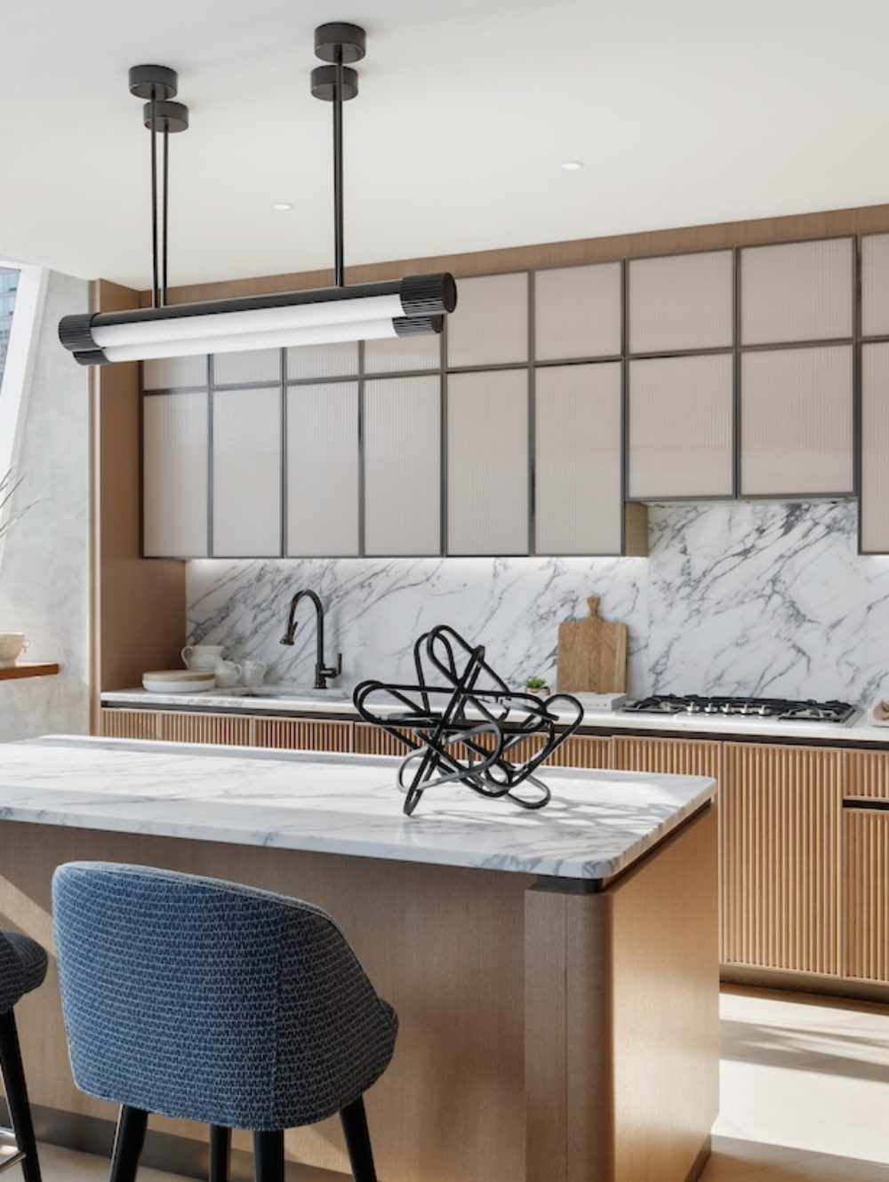 Kitchen at Lantern House luxury condos in NYC. Hardwood floors, center island, white countertops, and natural wood cabinets..