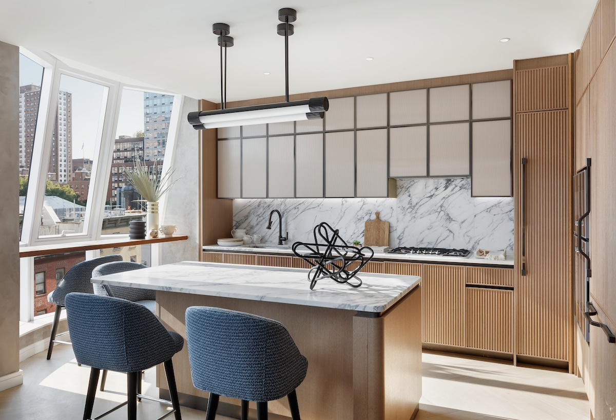 Kitchen at Lantern House luxury condos in New York. Natural wood finishes, white stone countertops and large windows.