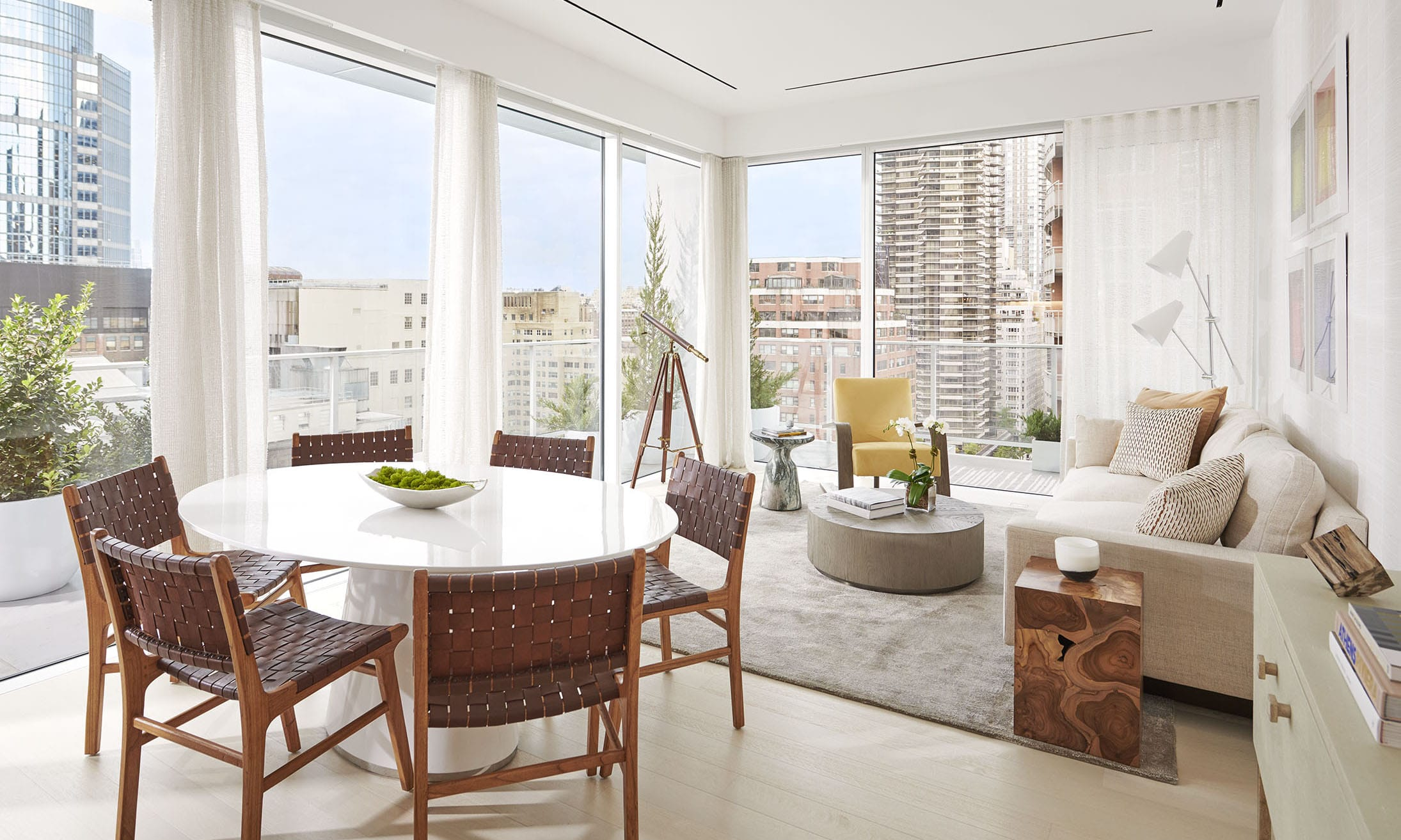 Corner living room with floor-to-ceiling windows, white table, and a tan couch overlooking New York at 200 E 59 condos.