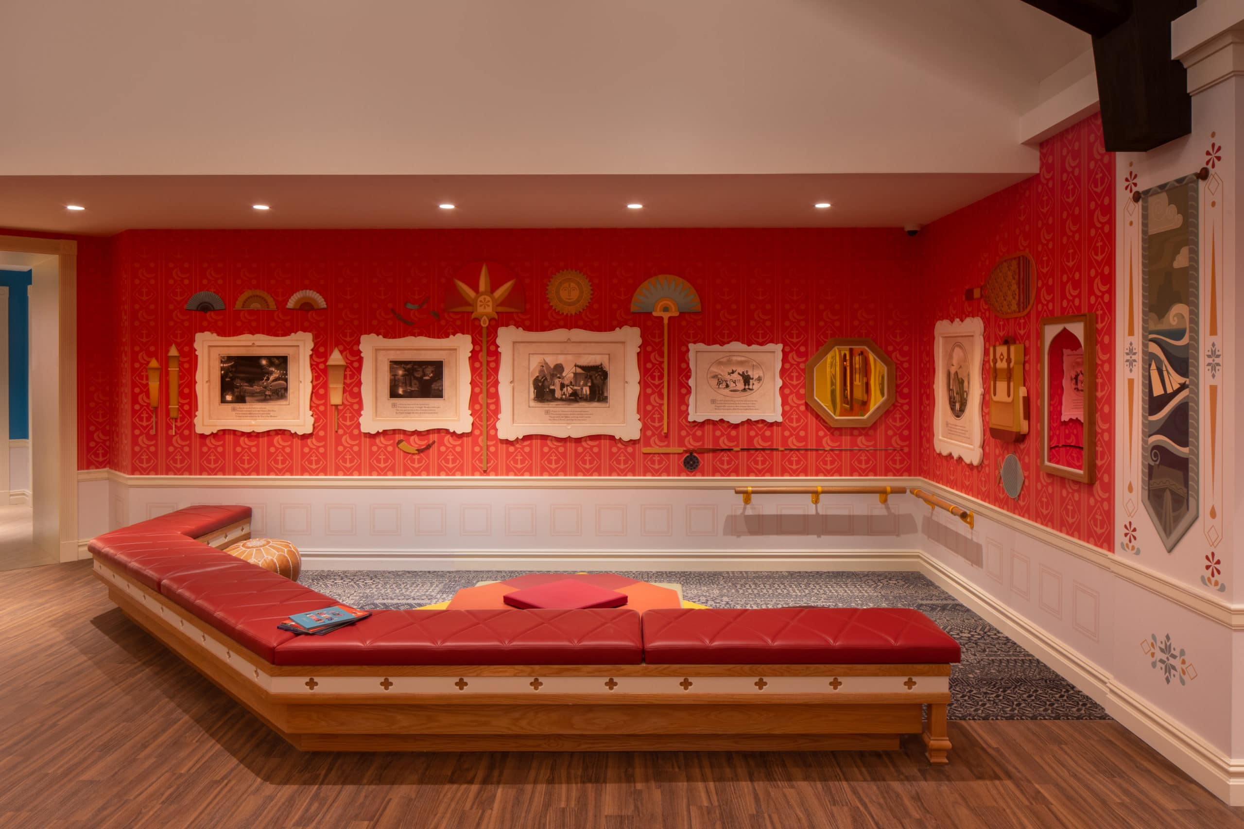 Seating area in the playroom at Waterline Square in NYC. Long crescent shaped red bench, red and white walls with paintings.