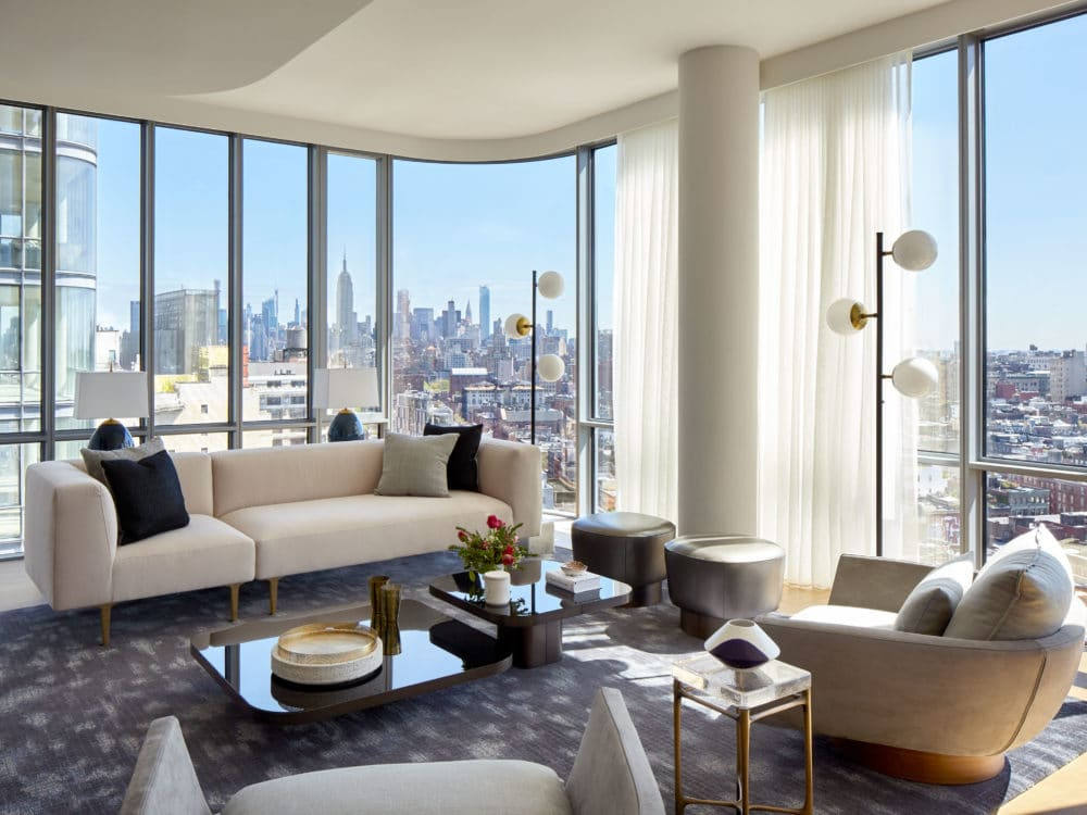 Interior view of 565 Broome residence living room with window view of New York City. Has full furniture and white walls.