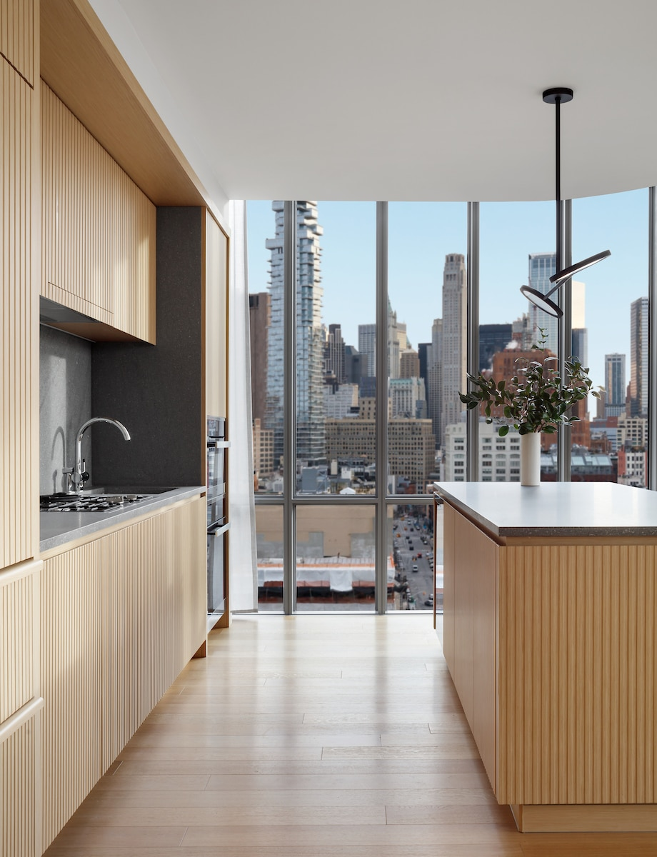 Interior view of 565 Broome residence kitchen with window view of New York City. Has wood floors and cabinets.