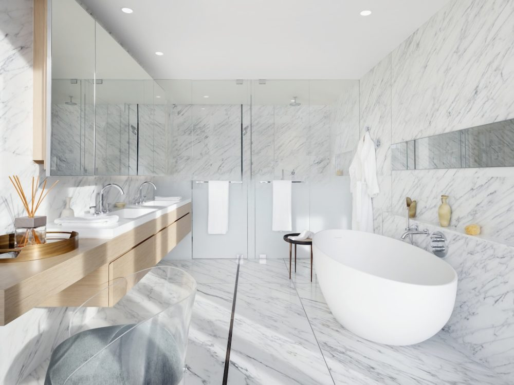 Interior view of 565 Broome residence bathroom in New York City. Has marble floors and walls, a sink and a white bathtub.