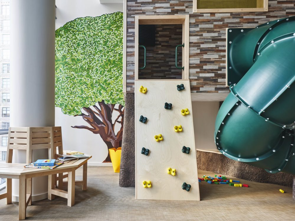 Interior view of 565 Broome residence children's playroom in New York City. Has green slide, rock wall and wooden chairs.