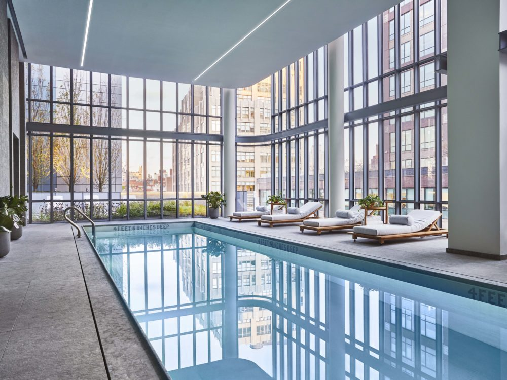 View of 565 Broome residence indoor pool with window view of New York City. Has longue chairs and rectangular pool.