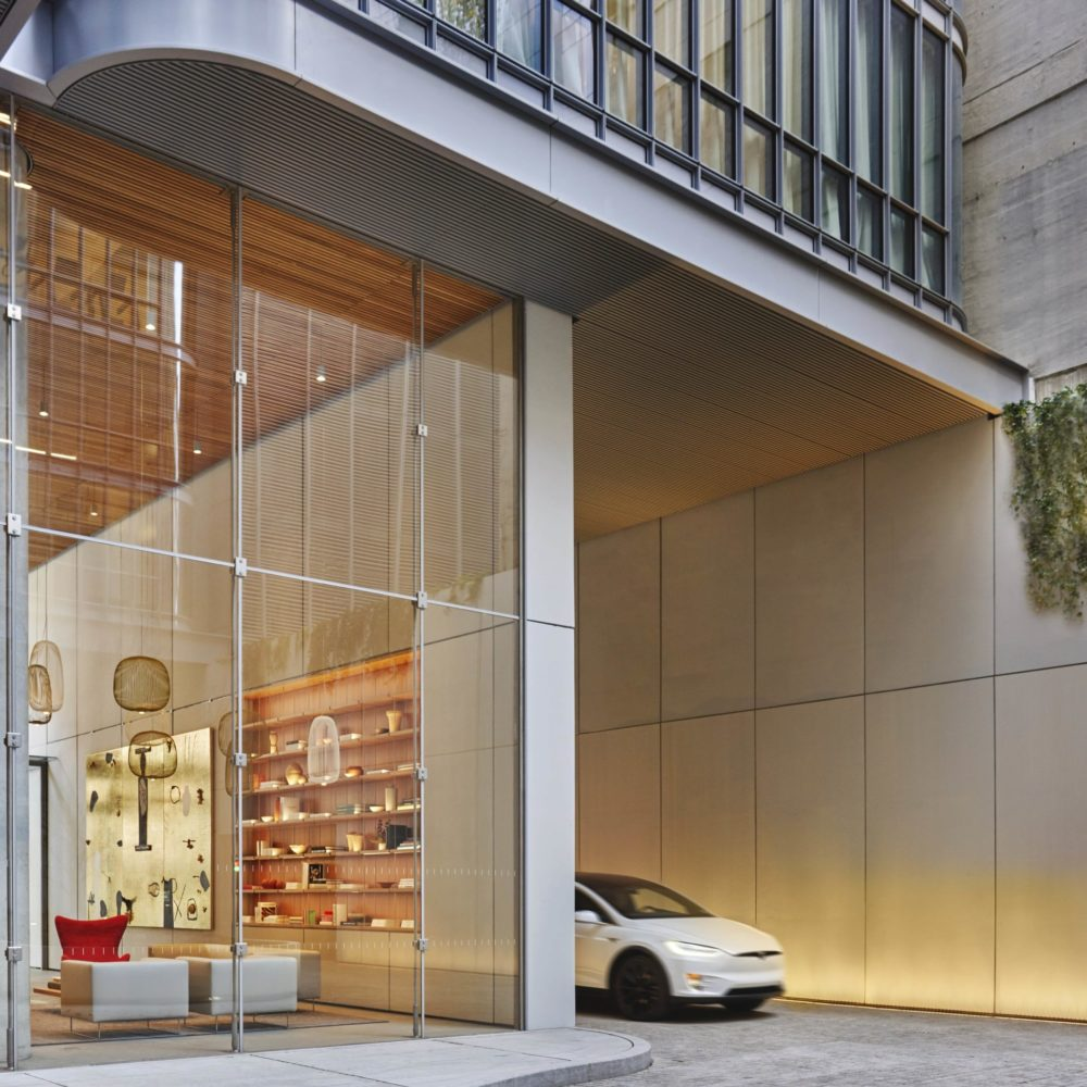 Exterior view of 565 Broome condominiums entrance and porte cochere in New York City. Has a white car parked outside.