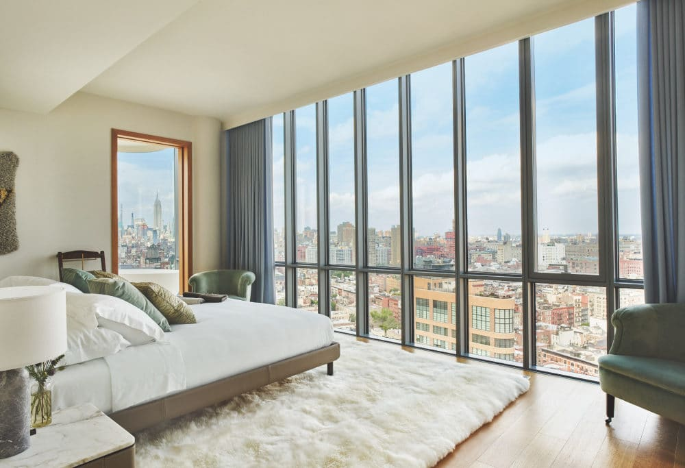 Interior view of 565 Broome residence master bedroom with window view of New York City. Has white walls, bed and rug.
