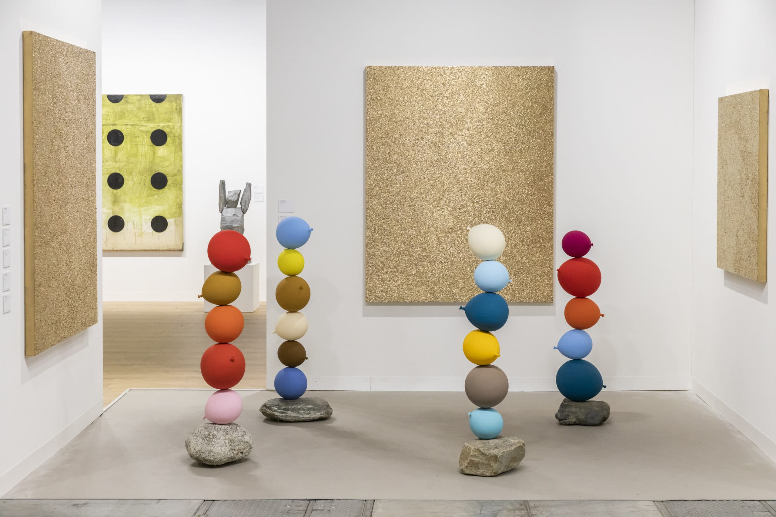 Interior view of art gallery in Miami. Includes 4 colored rock structures surrounded by gold artwork and a white wall.