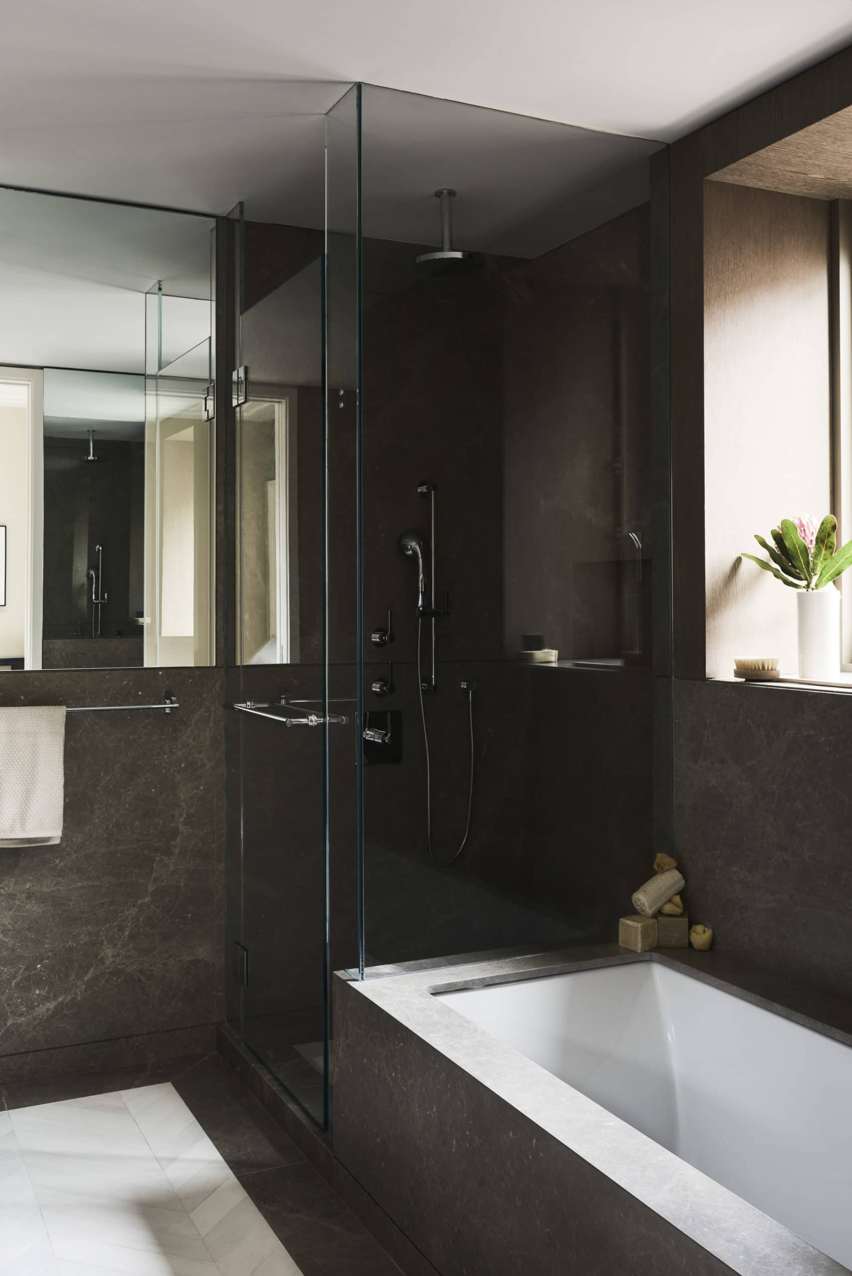 Bathroom at 40 Bleecker St residences in New York. Glass standing shower, soaking tub, and black stone walls with veining.
