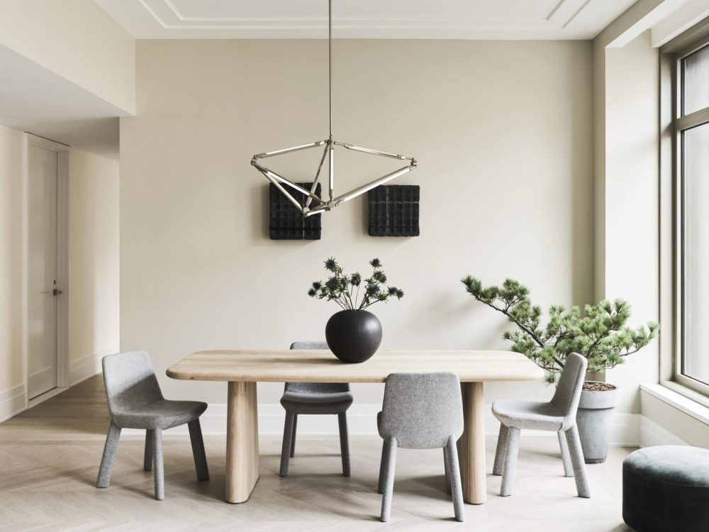 Dining room at 40 Bleecker St residences in NYC. Light colors, dining room table and large windows providing city views.