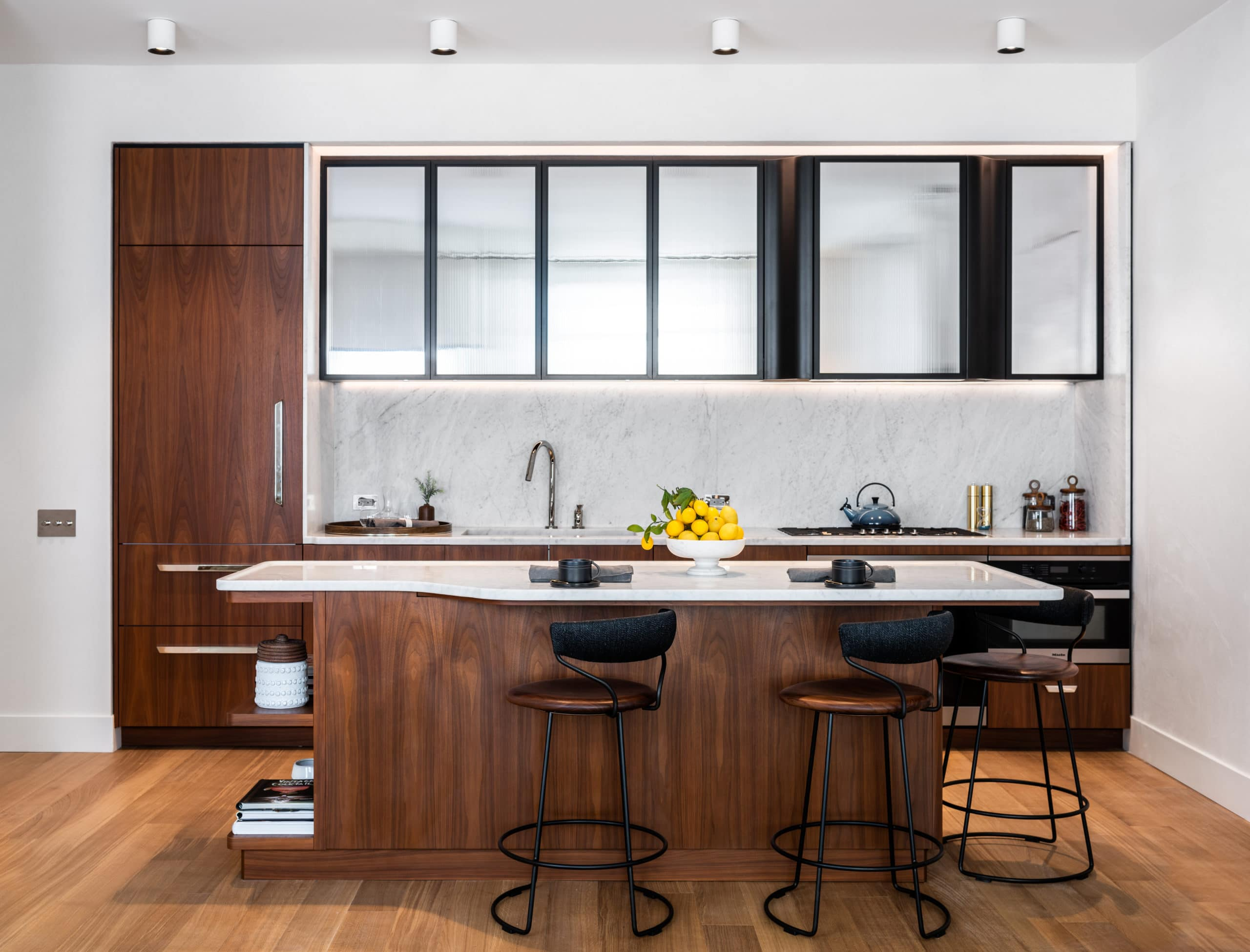 Kitchen in Greenwich West luxury condos in New York. Center island, stone countertops, white backsplash and glass cabinets.