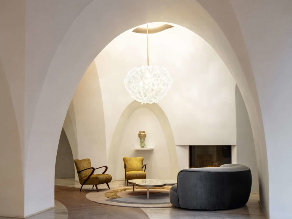 Interior arched, white hallway inside 180 E 88th street condominiums. Includes dark furniture and is in New York City.