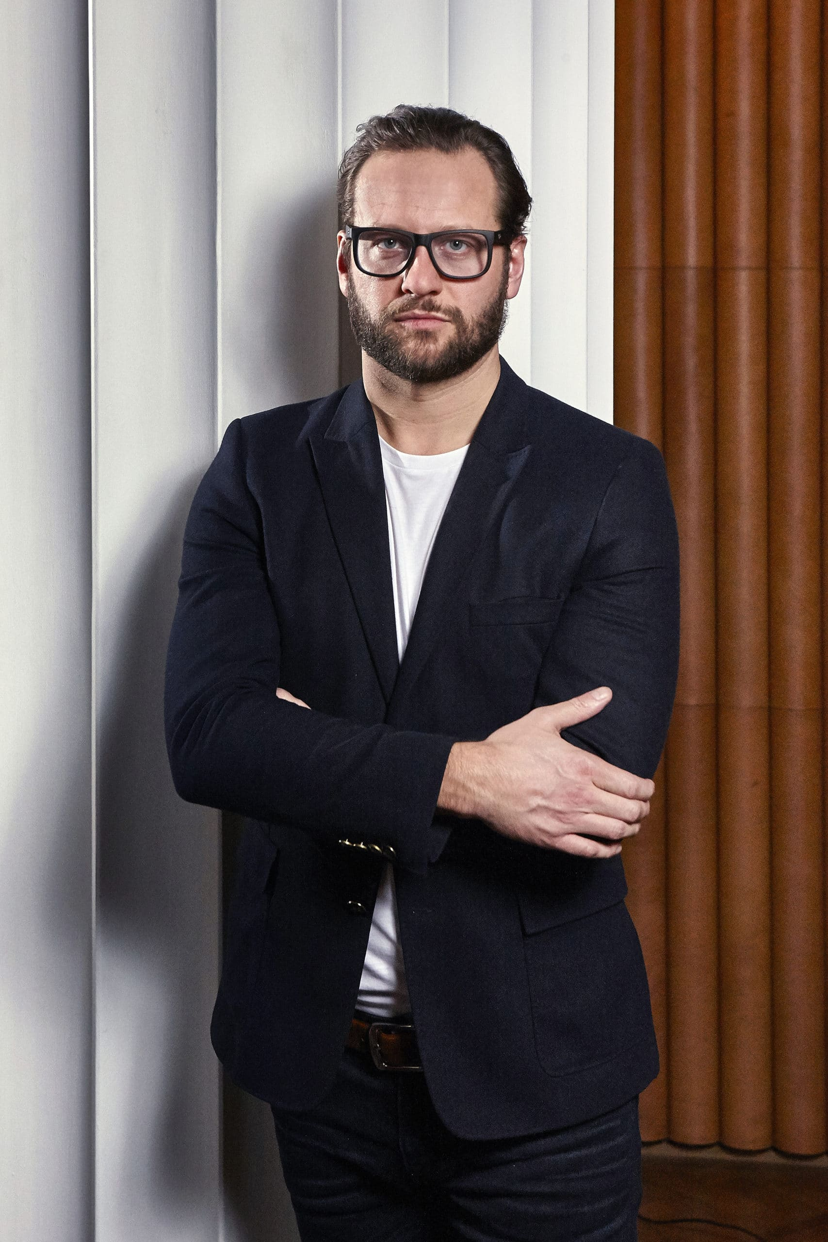 Profile picture of Elliot March standing with his arms crossed. Man wearing glasses, navy suit jacket, and white T-shirt.
