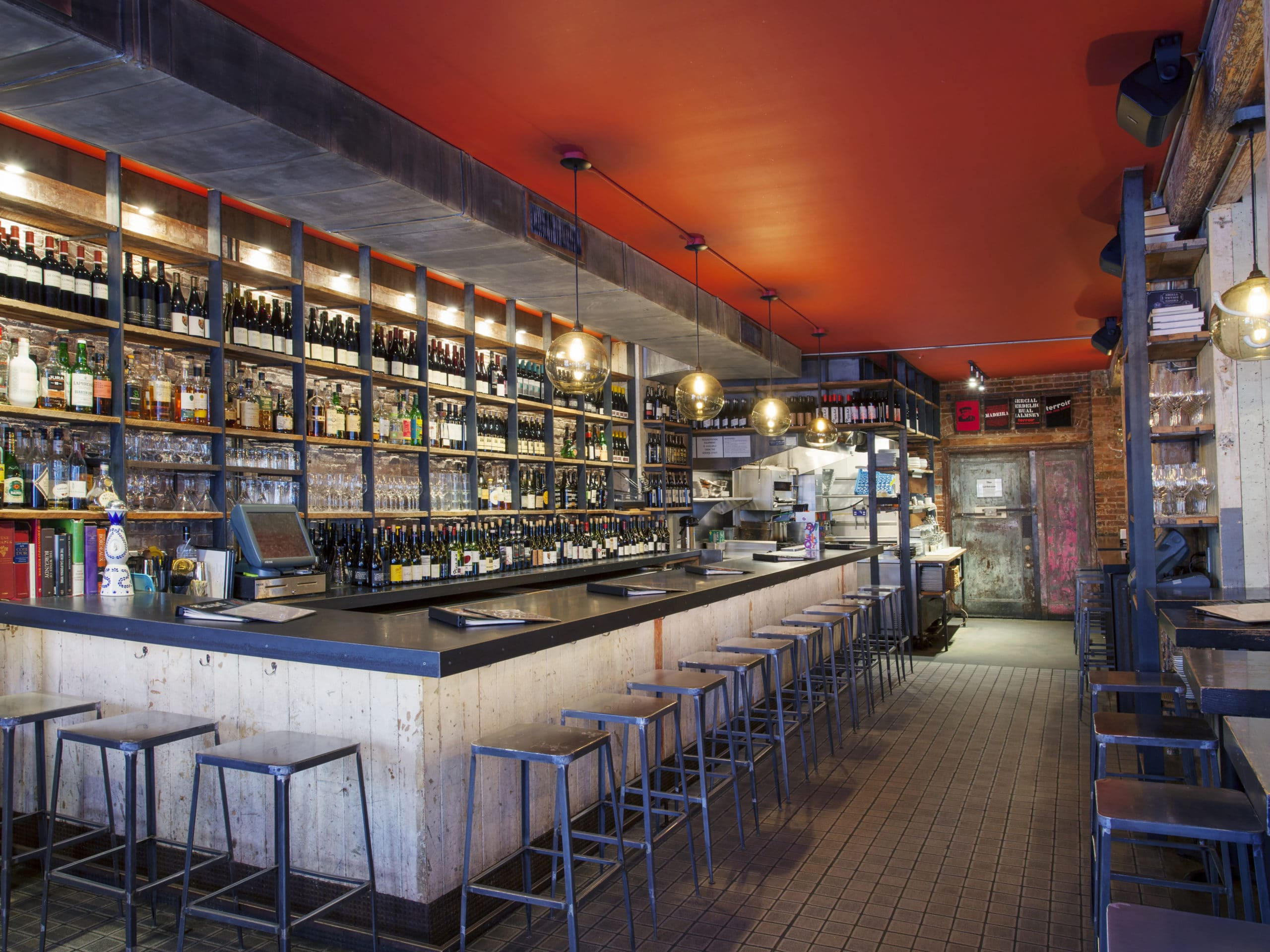 Residents wine bar at 30 Warren luxury residences in NYC. L-shaped bar with stools and wine bottles on the back shelves.