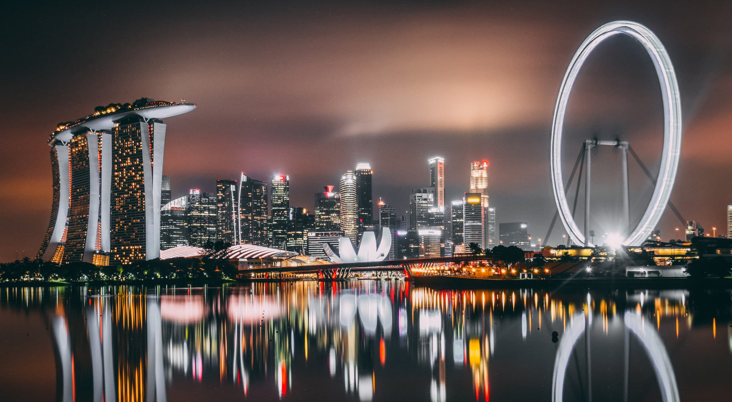 Night-time view of Marina Bay Promenade in Singapore. Large ferris wheel and towers glowing white with reflection in the bay.