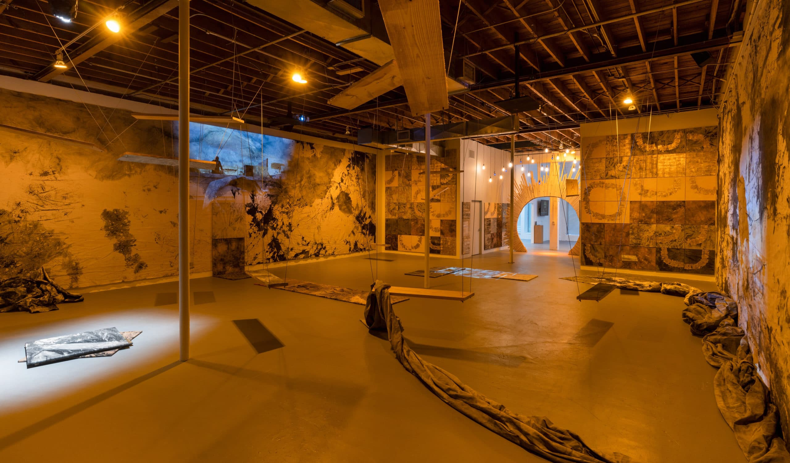 Installation view of at Locust Projects made by Dusk. Has a dimly lit interior and patterned walls.