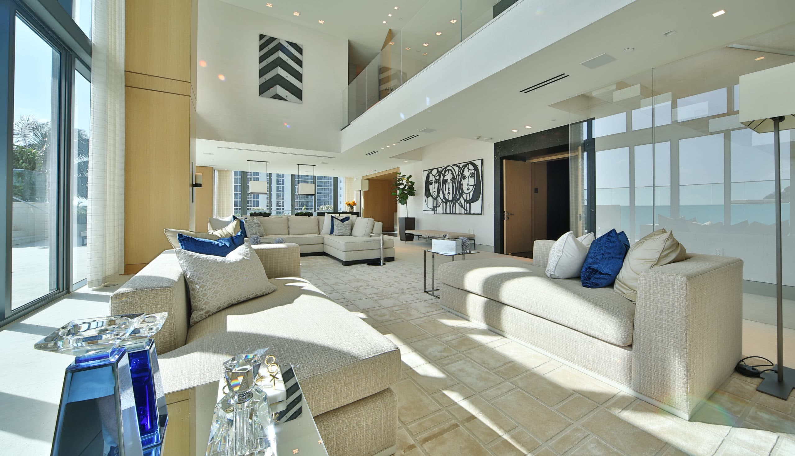 Interior of the Regalia Residences beach house in Miami. Living room furniture, high ceilings, and floor to ceiling windows.