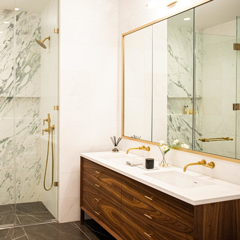 Bathroom at Rosehill residences in New York. Standing shower with white marble, a dark wood vanity and white countertop.