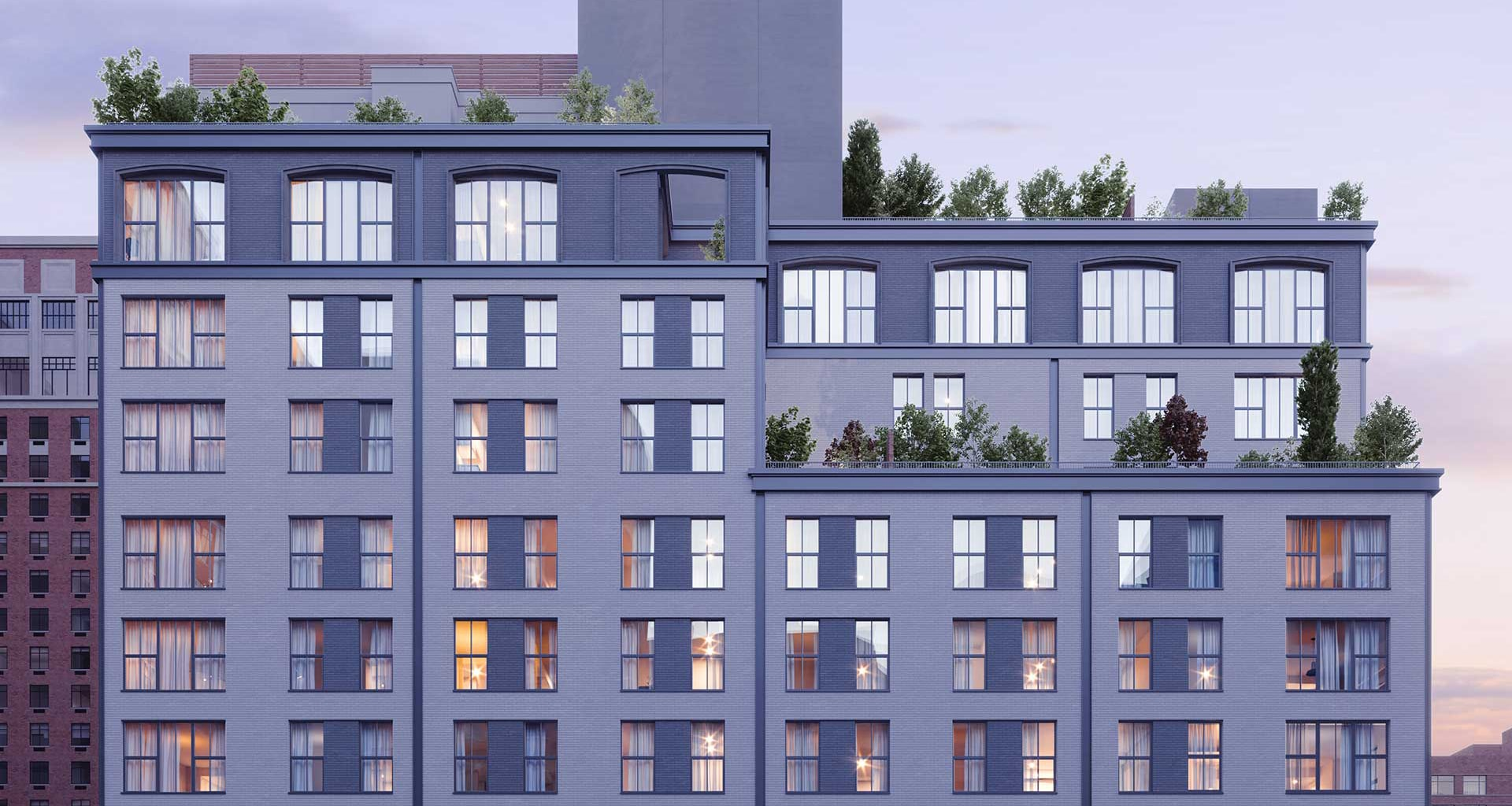Exterior view of top floors at The Symon luxury condos in New York City. Tiered rooftop terraces with brown and grey brick.